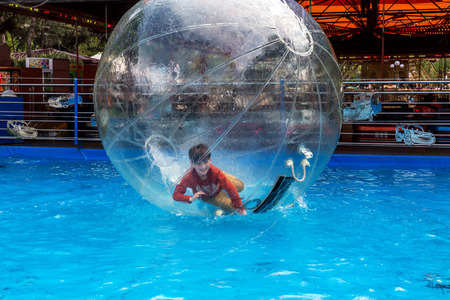 Odessa, Ukraine - May 6, 2019. Little children in an inflatable balloon, having fun on the water. The ball in the water - fascinating summer attractions for children. Water zorbing Banque d'images - 127551242
