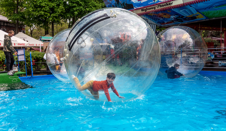 Odessa, Ukraine - May 6, 2019. Little children in an inflatable balloon, having fun on the water. The ball in the water - fascinating summer attractions for children. Water zorbing Redactioneel