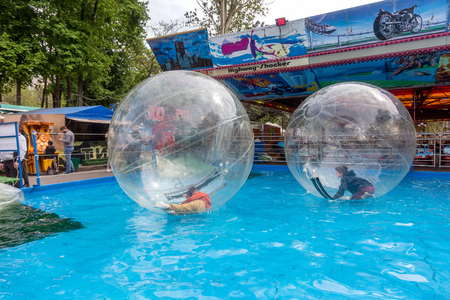 Odessa, Ukraine - May 6, 2019. Little children in an inflatable balloon, having fun on the water. The ball in the water - fascinating summer attractions for children. Water zorbing 에디토리얼
