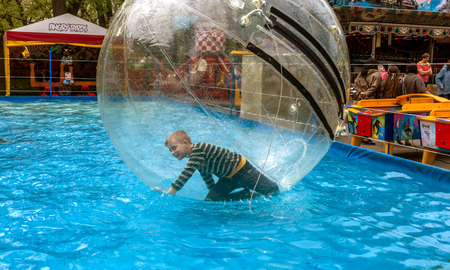 Odessa, Ukraine - May 6, 2019. Little children in an inflatable balloon, having fun on the water. The ball in the water - fascinating summer attractions for children. Water zorbing Editorial