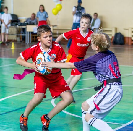 ODESSA, UKRAINE - MAY 18, 2019: Young children play rugby during final games of championship in hall. Children's sport. Children play rugby 5. Fight for victory of children in rugby Publikacyjne