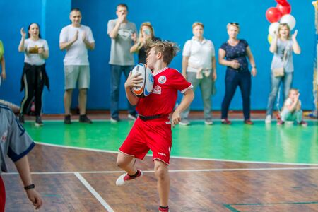 ODESSA, UKRAINE - MAY 18, 2019: Young children play rugby during final games of championship in hall. Children's sport. Children play rugby 5. Fight for victory of children in rugby
