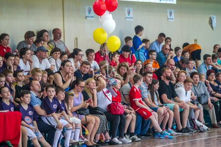 ODESSA, UKRAINE - May 18, 2019. Spectators, fans in stands of gym are emotionally supported by team of children's rugby championship 5. Parents and children are having fun enjoying rugby tournament Publikacyjne