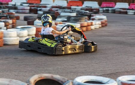 ODESSA, UKRAINE - June 19, 2019: karting. Racers on races on special safe high-speed tracks limited by car tires. Attraction High-speed ride in carts. Sport karting entertainment