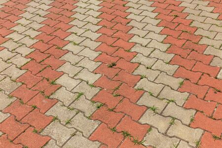 Street background of old paving stone. Background of old cobblestone pavement close-up. Old paving tiles, green grass growing among them, texture of paving stones and green grass, close-up, top view