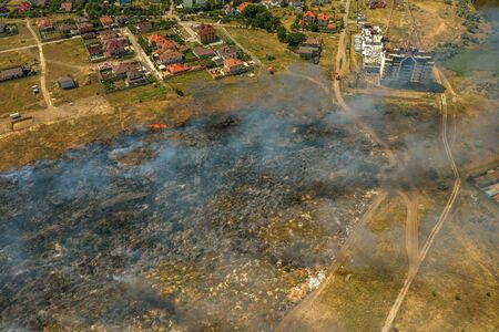 Heavy smoke in steppe. Forest and steppe fires destroy field, steppes during severe droughts. Fire, strong smoke. Blur focus due to shaking hot fire. Disaster, damage, risk to homes. View from drone
