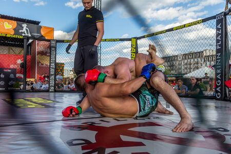 ODESSA, UKRAINE-June 30, 2019: Fighters of MMA boxers are fighting without rules in cage ring of octagons. MMA fighters in ring at  championship. Look at boxing fights without rules through metal cage Editoriali