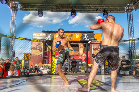 ODESSA, UKRAINE-June 30, 2019: Fighters of MMA boxers are fighting without rules in cage ring of octagons. MMA fighters in ring at  championship. Look at boxing fights without rules through metal cage Editorial