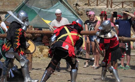 ODESSA, UKRAINE - JULY 20, 2019: Battle of the Knights with medieval weapons at the medieval performance. Knights fight on the field during the battle tournament of the festival of medieval culture