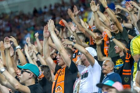 ODESSA UKRAINE - July 28, 2019: spectators at stadium. Crowds of fans in stands of football stadium during match Shakhtar (Donetsk) -Dynamo (Kiev). Grandstand with fans. Stands with football fans