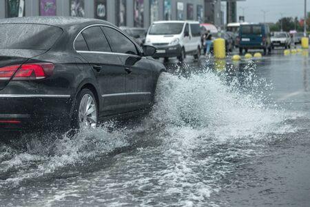 Conduire une voiture sur une route inondée lors d'inondations causées par des pluies torrentielles. Les voitures flottent sur l'eau, inondant les rues. Éclaboussure sur la voiture. Route urbaine inondée avec une grande flaque d'eau