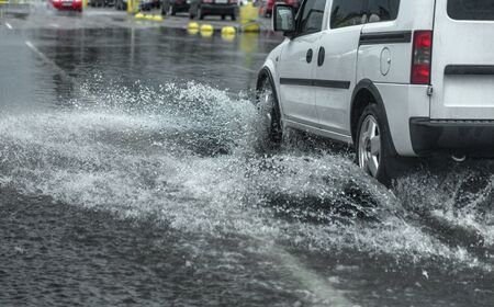 Odessa, Ukraine - August 9, 2019: driving car on flooded road during flood caused by torrential rains. Cars float on water, flooding streets. Splash on the car. Flooded city road with a large puddle Sajtókép