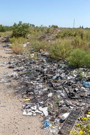 Plastic bottles bags and other household garbage were thrown along road. Garbage on side of road. Environmental pollution concept. Spontaneous illegal dumping of unnecessary household waste along road