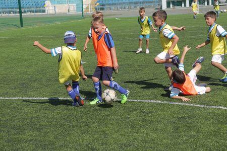 Odessa, Oekraïne - 7 september 2019: kleine kinderen in opleiding voetballen. Jongere jongens trappen voetbal op de speelplaats. Kinderen voetballen op een groen zaalvoetbalveld Redactioneel