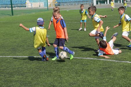 ODESSA, Ucrania - 7 de septiembre de 2019: los niños pequeños en el entrenamiento juegan al fútbol. Los niños más pequeños patean fútbol en el patio de recreo. Los niños juegan al fútbol en un campo de fútbol sala verde. Editorial