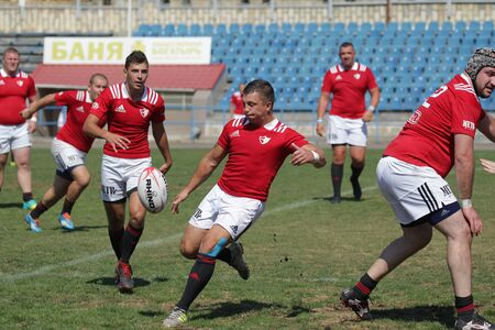 ODESSA, UKRAINE - SEPTEMBER 7, 2019: National team of Odessa Rugby Championship - Kremenchug. Intense struggle of rugby players for ball. Dynamic game on green field of stadium. Fierce Rugby Fight