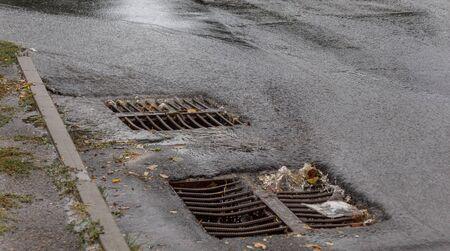 Flujo de agua durante las lluvias intensas y la obstrucción de las aguas residuales de la calle. El flujo de agua durante un fuerte huracán en las alcantarillas pluviales. Sistema de alcantarillado pluvial a lo largo de la carretera para drenar la lluvia en el sistema de drenaje Foto de archivo