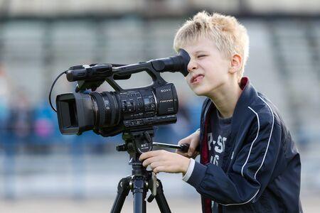 Odessa, Ukraina - OKOŁO 2019: Mały chłopiec, nastolatek, nagrywa wideo 4K na profesjonalnej kamerze wideo na zielonym polu stadionu. Młody filmowiec z kamerą telewizyjną Publikacyjne