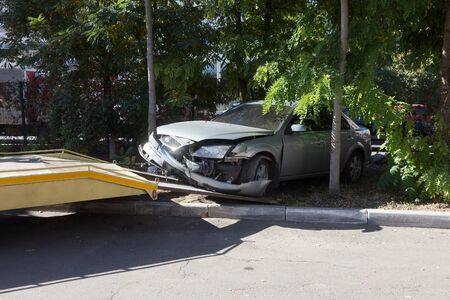 accidente automovilístico, colisión frontal. Camión de remolque carga un coche destrozado tras un accidente
