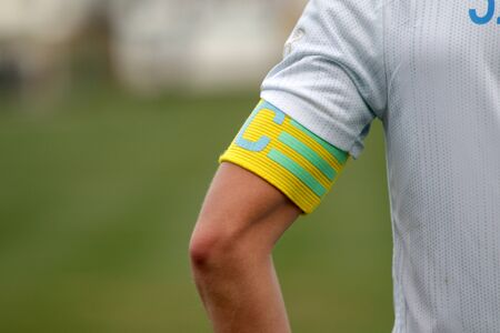 Captain of the football team on the stadium field. Sports background-the hand of the team captain with the identifying distinctive ribbon of the captain, official leader of team of footballers