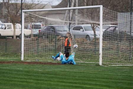 ODESSA, UKRAINE - CIRCA 2019: A goalkeeper of a local football team makes a save while playing in a regional derby championship on a bad football field. Soccer goal, goal net