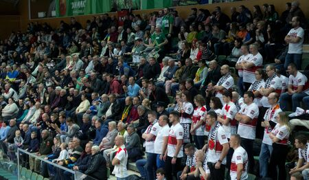Odessa, Yuzhny, Ukraine-November 27, 2019. Group of fans with flags of Poland in stands during European volleyball championship among women. VK Khimik - LKS Kommersant Poland (black). Group tournament 報道画像