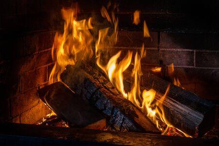 Feu dans une cheminée vintage vintage. Le bois de chauffage et les charbons brûlent par la cheminée pour faire frire la viande sur un feu