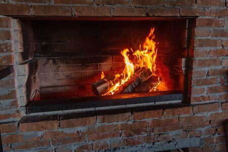 Feuer in einem Vintage-Kamin. Brennholz und Kohlen brennen durch den Kamin, um Fleisch auf einem Feuer zu braten