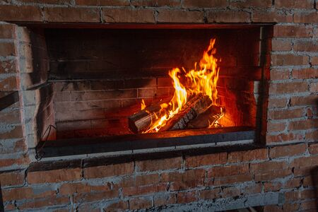 Fuoco in un caminetto vintage vintage. Legna da ardere e carboni bruciano attraverso il camino per friggere la carne sul fuoco
