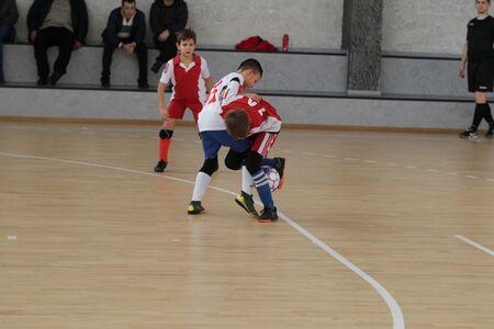 Odessa, Ukraine-December 12, 2019: Little boys, children play mini football in sports hall at sports city Junior championship. Children's sport is healthy lifestyle. Sports children football players Editorial