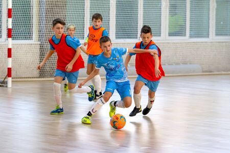 Odessa, Ukraine- Febr 17, 2020: Little boys, children play mini football in sports hall at sports city Junior championship. Children's sport is healthy lifestyle. Sports children football players