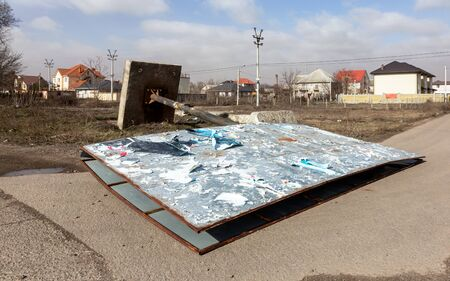 A street billboard is torn down by a strong wind on a stormy day during a hurricane. A strong gusty hurricane wind turned the billboard onto a car road