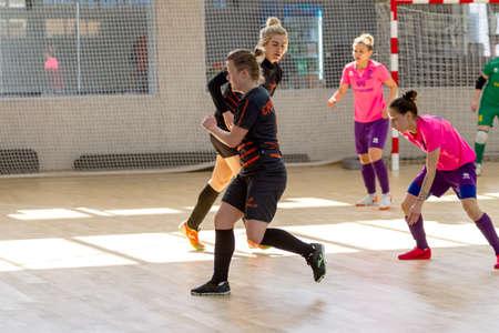 ODESSA, UKRAINE - March 13, 2020: Futsal Cup of Ukraine, futsal among students. During final match in futsal among student teams. Beautiful sports girls play mini football on parquet floor Redactioneel