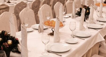 Festive table setting background. Serving a large festive restaurant table in anticipation of guests in a soft dim light.