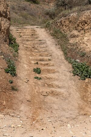 Worn steps of stone staircase are cut down by tourist along popular tourist route. Trail goes up stone stairs. Stone staircase in nature in coastal cliff. Natural stone staircase in landslide hillside