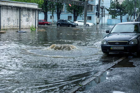 Odessa, Ukraine - May 28, 2020: driving car on flooded road during flood caused by torrential rains. Cars float on water, flooding streets. Splash on car. Flooded city road with large puddle