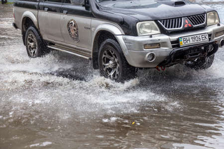 Odessa, Ukraine - May 28, 2020: driving car on flooded road during flood caused by torrential rains. Cars float on water, flooding streets. Splash on car. Flooded city road with large puddle Sajtókép