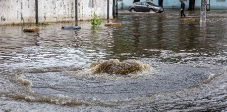 Flooding after heavy rains in city. Sewage broke open asphalt and blew up fountain. Dirty sewage broke through storm sewer and spilled onto streets of city after rain. Danger of epidemic and infection Foto de archivo