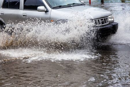 Ð'riving car on flooded road during flood caused by torrential rains. Cars float on water, flooding streets. Splash on car. Flooded city road with large puddle. Flooding after heavy rains at city