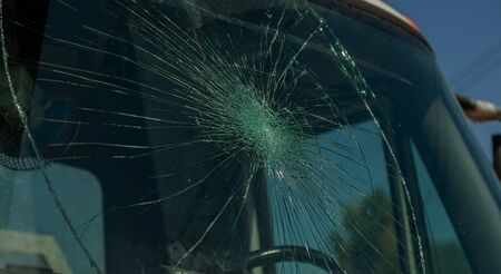 Broken car windshield. Web of radial cracks, crack on triple windshield. Broken windshield car, damaged glass with traces of an oncoming stone on road or trace of downed pedestrian or animal on road Imagens