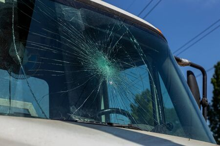 Broken car windshield. Web of radial cracks, crack on triple windshield. Broken windshield car, damaged glass with traces of an oncoming stone on road or trace of downed pedestrian or animal on road