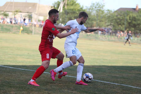 ODESSA, UKRAINE - Fight of the first league football clubs at the Ukrainian championship. FC BALKANY (Zorya) - FC VOLYNB (Lutsk) - red. A dramatic duel while playing big football on a grass field Editorial