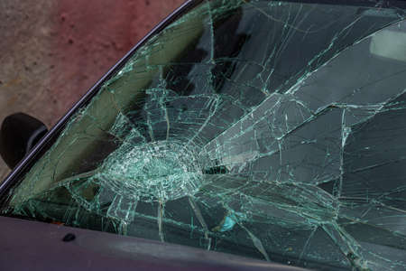Selective focus image on the broken windshield of the car. Car accident. Broken windshield of a car after an accident with fatalities Foto de archivo - 152007560