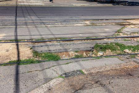 Damaged asphalt road with potholes. Bad road Bad asphalt. Broken road with tram rails, cracks, pits, potholes in the asphalt