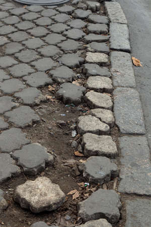 Damaged road with potholes, caused by freeze-thaw cycles in winter. Bad road. Broken pavements paving slabs on sidewalk. Pavement with paving slabs with defects and cracks coming in perspective