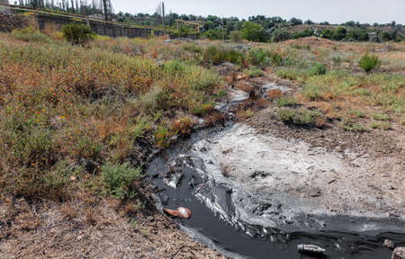 Spilled streams of liquid crude oil flow down drainage ditch into public body of water. Environmental disaster Oil pollution of environment from obsolete technologies and ancient production equipment