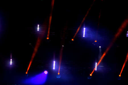 Stage lights. Background in show. Light spotlight in the dark. The interior of the theater scene is illuminated to the projector. Stage lights and stage smoke during the concert