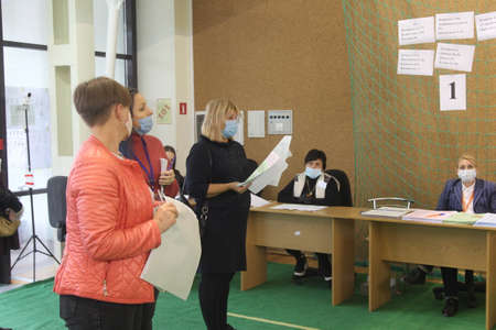 ODESSA, UKRAINE -25.10.2020 - Elections in Ukraine. Electoral platform for elections of local councilors during the COVID-19 coronavirus pandemic. People wearing masks and gloves with voting ballots