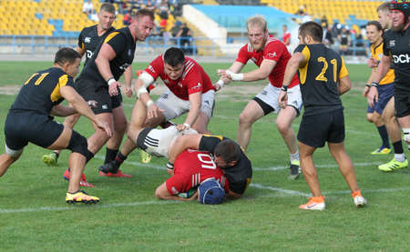 ODESSA, UKRAINE -2020.10.17 - Final of Ukrainian rugby championship CREDO (Odessa) - red, OLYMPIK (Kharkiv) black Intense struggle of rugby players for ball. Dynamic game on green field. Brutal rugby Editorial