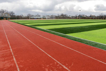 Sports stadium with artificial turf green grass on a professional football field. Running Artificial Rubber Stadium Sports Tracks Imagens